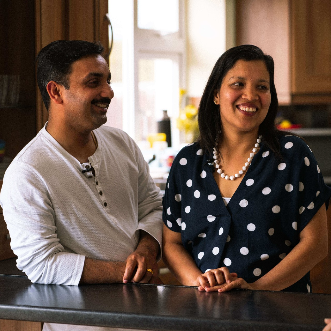 Biji & Sithosh smiling together in the kitchen of their new home.