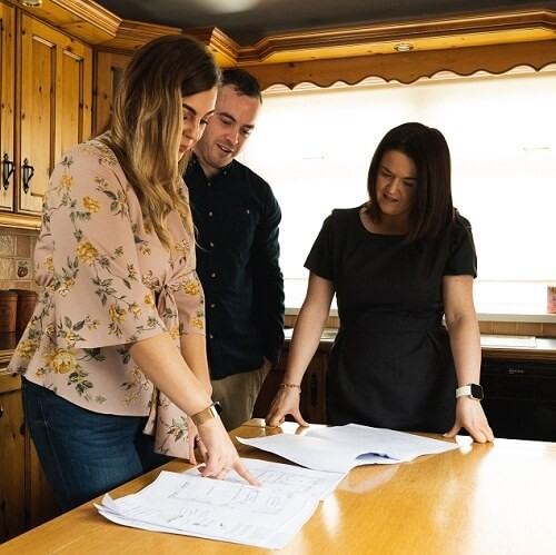 Customers Melissa and Darren with their mortgage advisor looking at papers on a table.