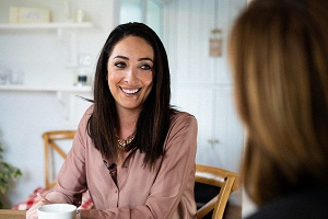 A customer, Aisling, smiles as she sits having a cup of tea and chatting with a mortgage advisor at home.