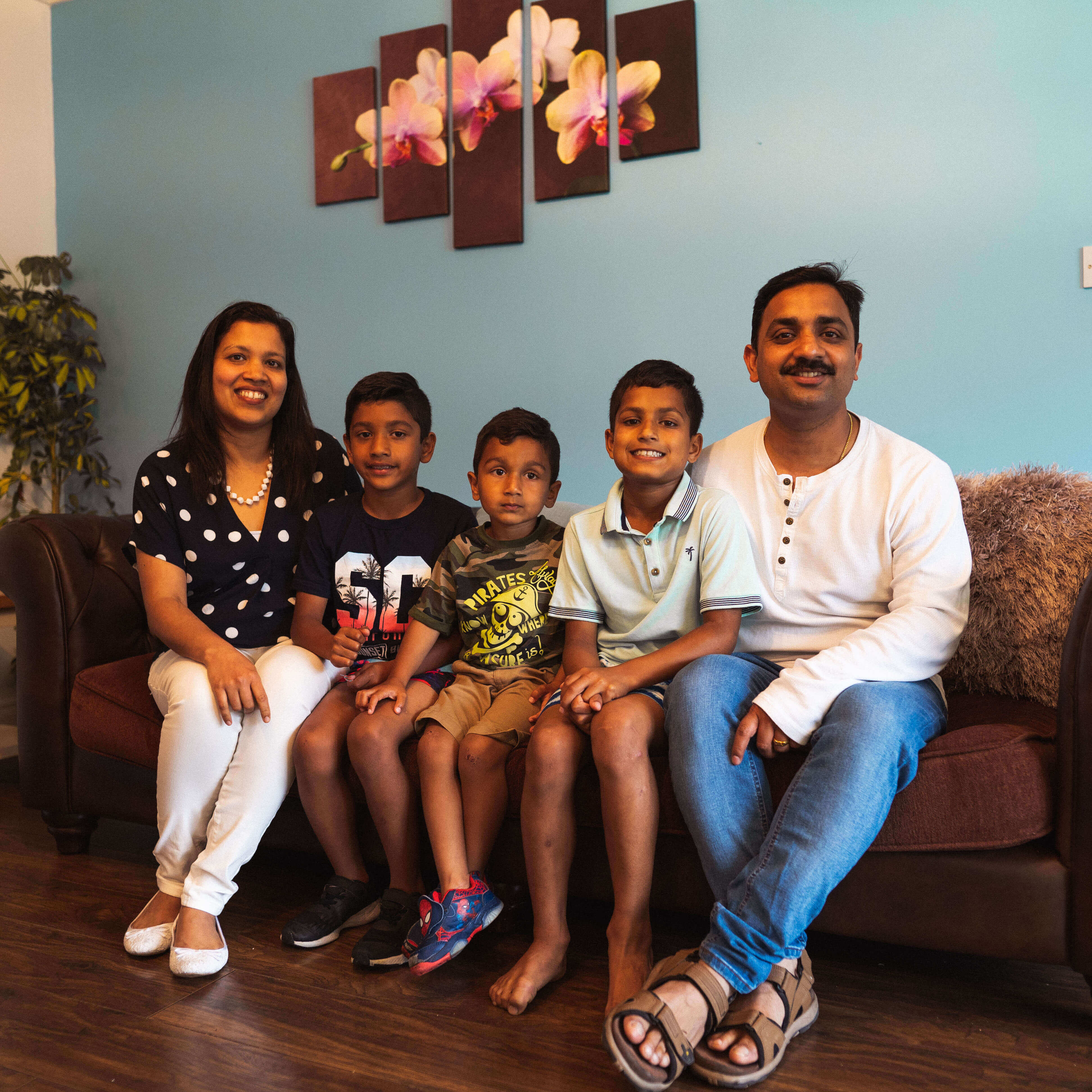 Biji and Sithosh sitting together with their three sons.on a couch in their new home.
