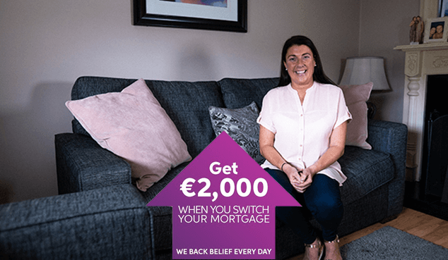 First time buyer Elaine smiling happily as she sits on couch in her new home.