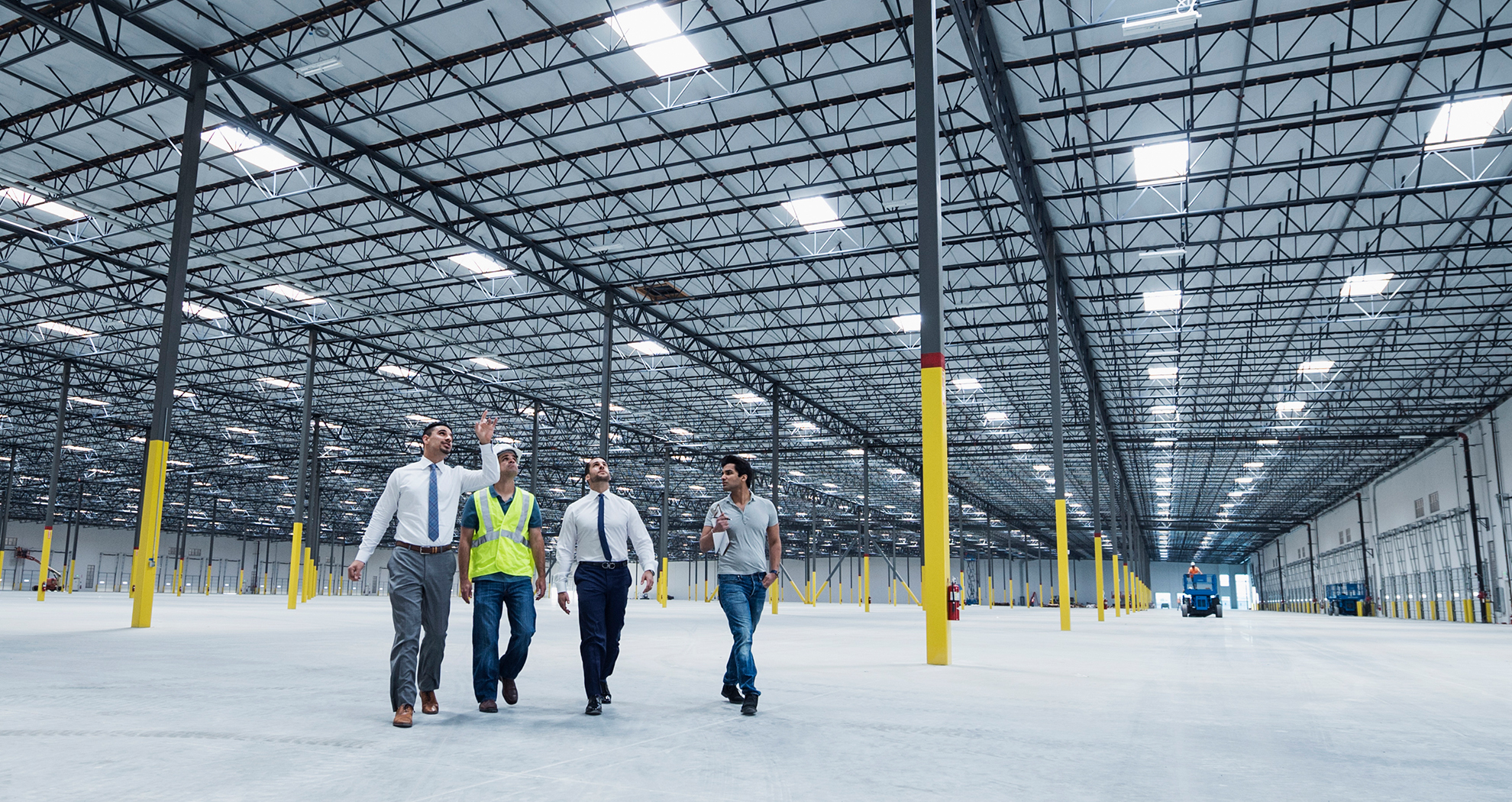 Four men inside a newly rennovated production facility looking at the ceiling