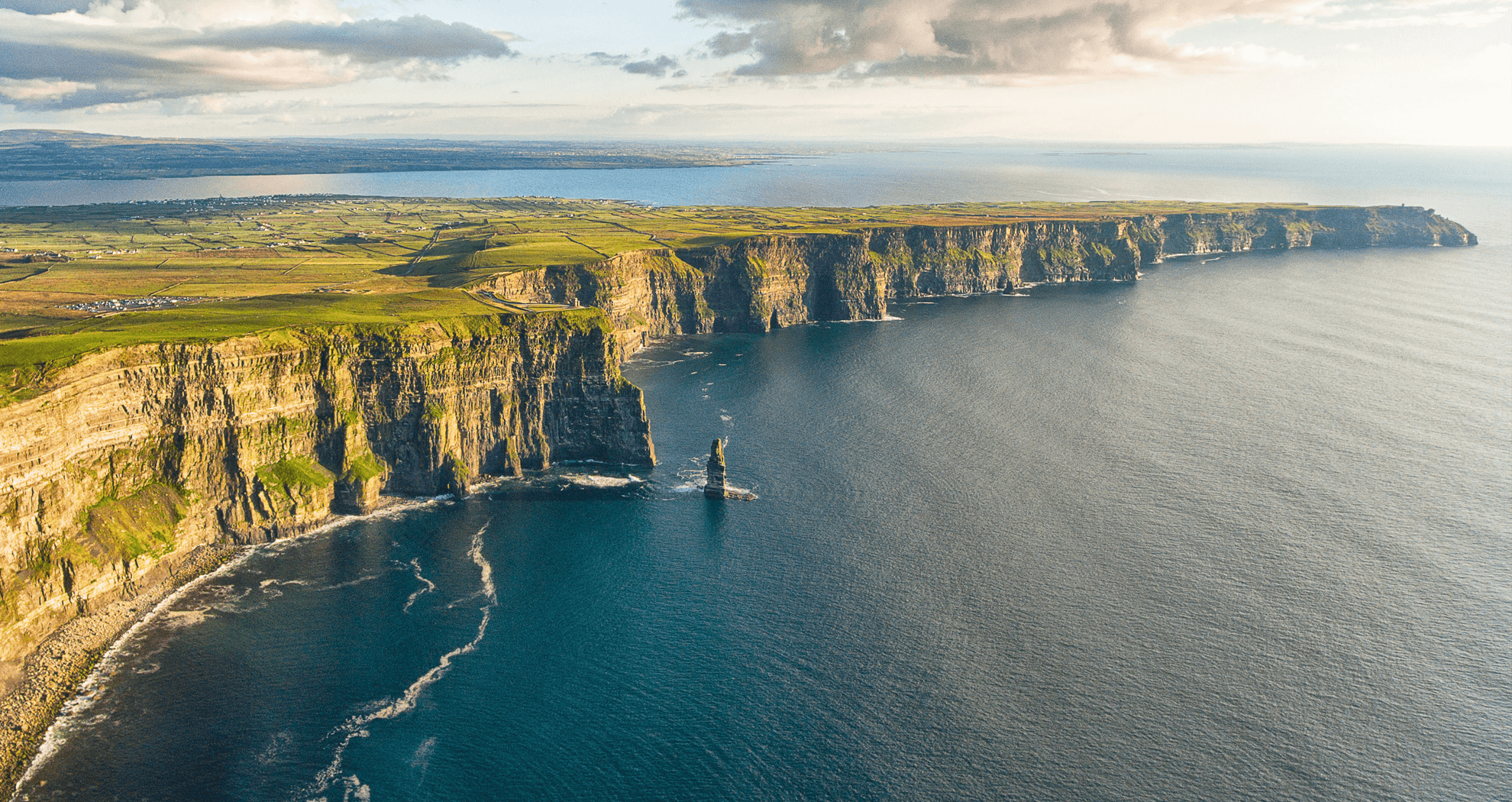 A wide aerial view of the Cliffs of Moher.